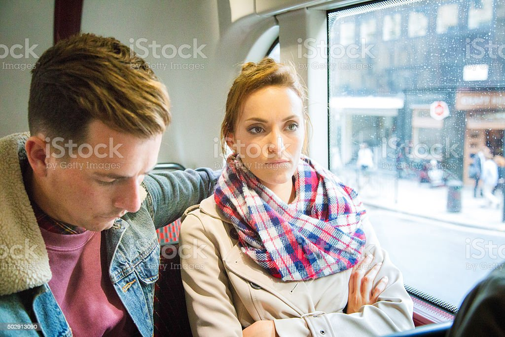Unhappy upset woman on bus with remorseful boyfriend stock photo