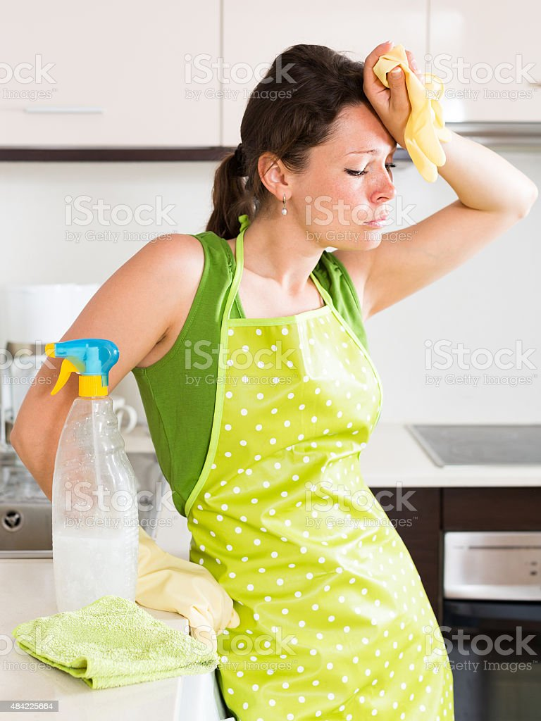 Unhappy woman cleaning furniture stock photo