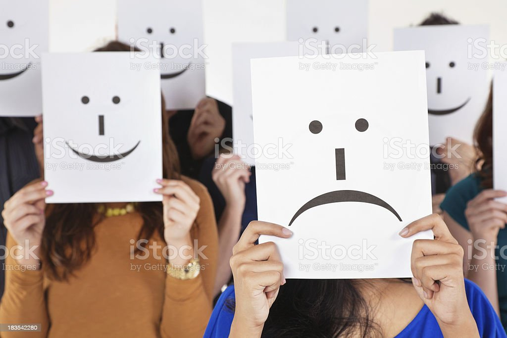 Unhappy Woman Holding Sad Face Sign Surrounded By Happy People stock photo