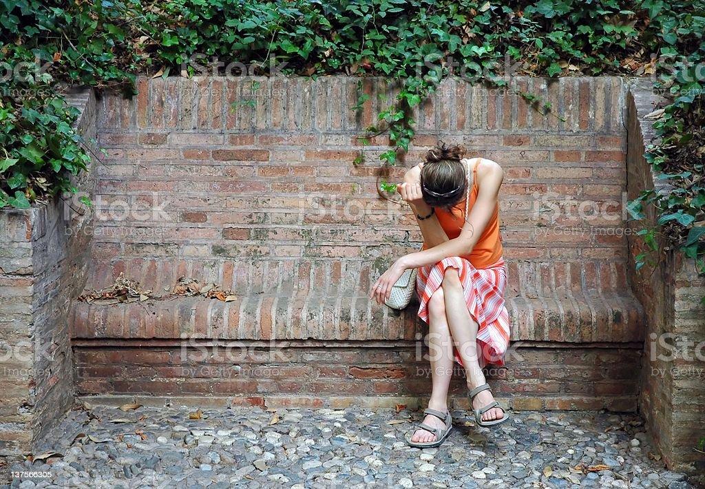 unhappy woman in orange dress sitting on the stony bench stock photo