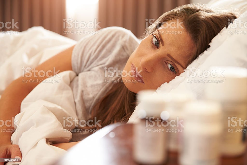 Unhappy Woman Looking At Medication On Bedside Table stock photo
