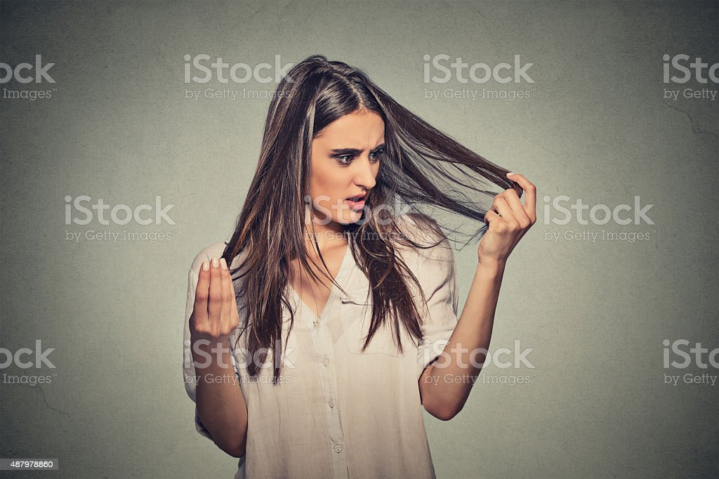 unhappy woman surprised she is losing hair stock photo