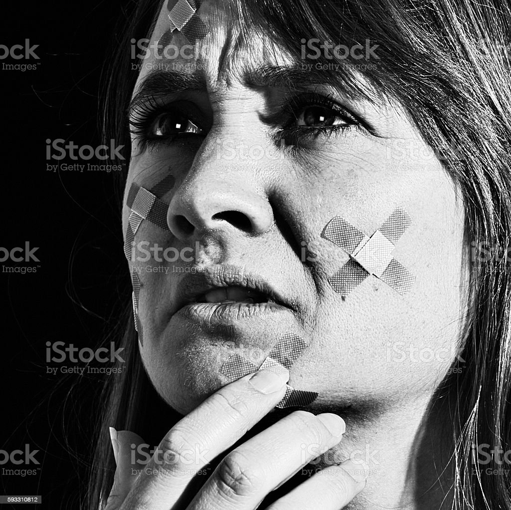 Unhappy woman touching her face covered with adhesive bandages stock photo