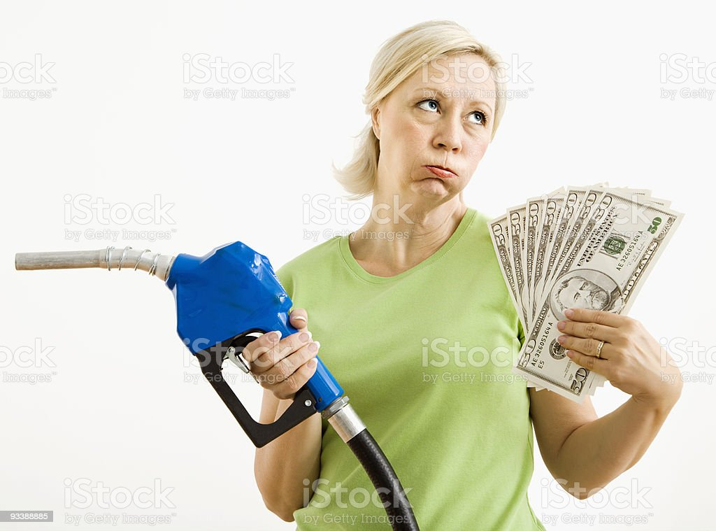 Unhappy woman with gas pump and money. royalty-free stock photo