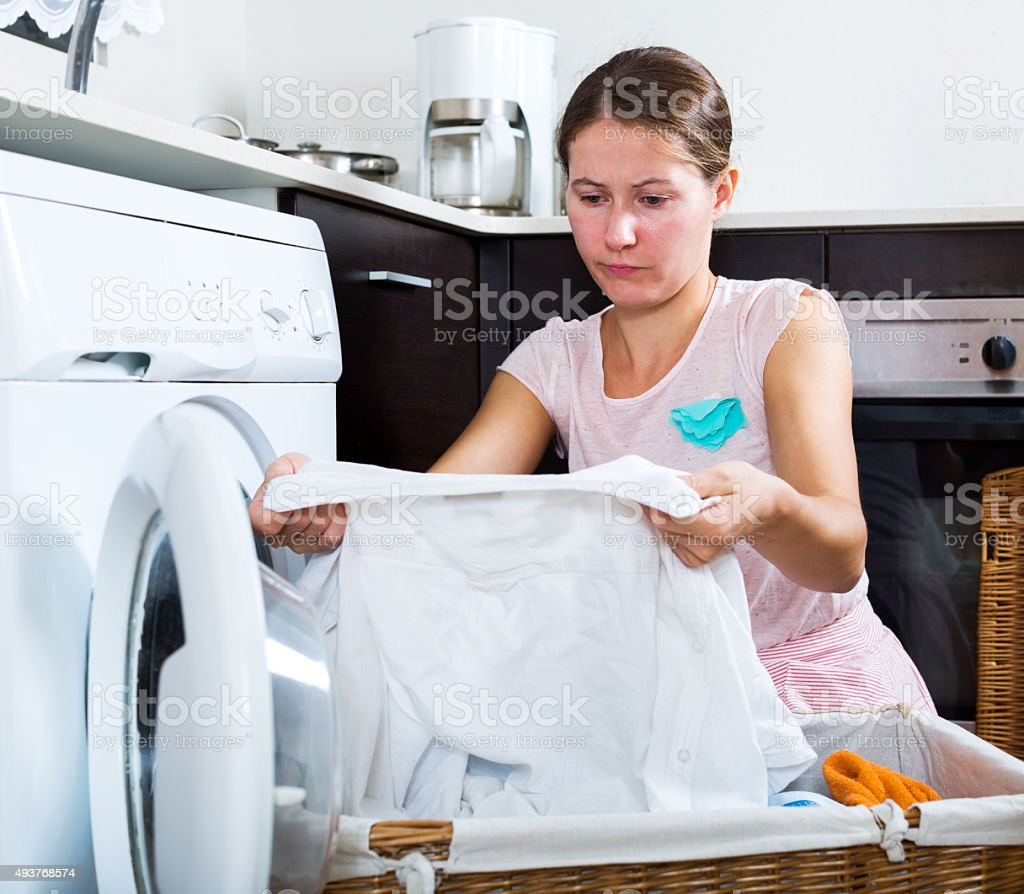 Unhappy woman with washing machine stock photo