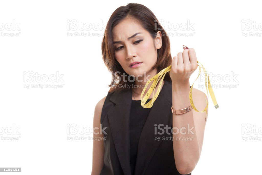 Unhappy young Asian woman with measuring tape. stock photo