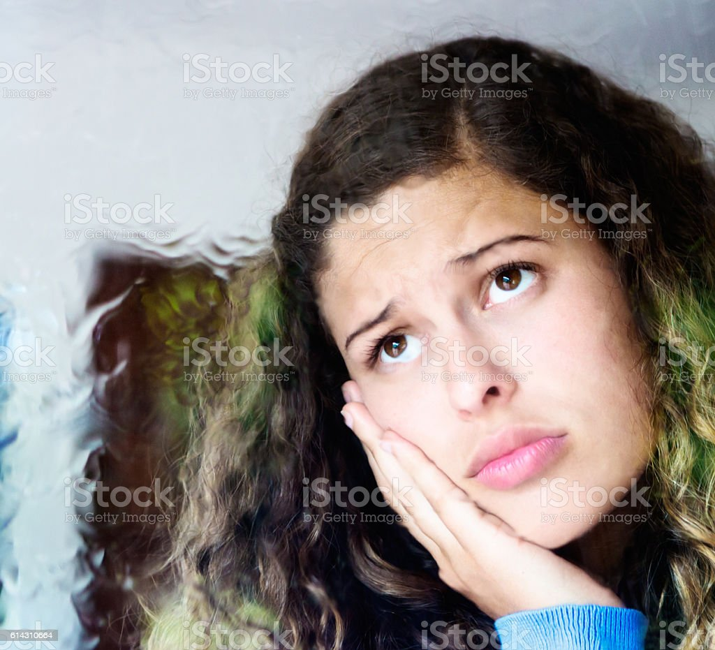 Unhappy young beauty frowning through window at the rain outside stock photo