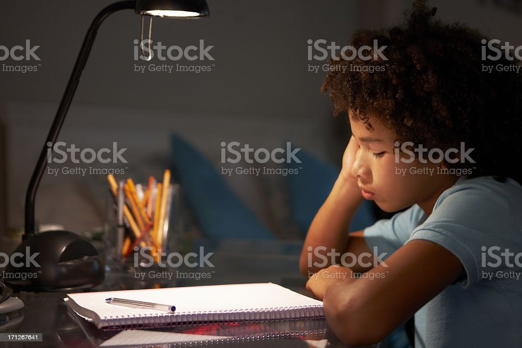 Unhappy Young Boy Studying At Desk stock photo