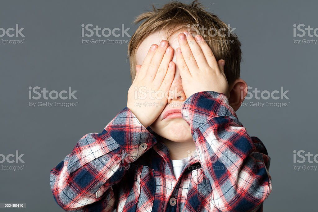 unhappy young child covering his eyes with hands for sadness stock photo