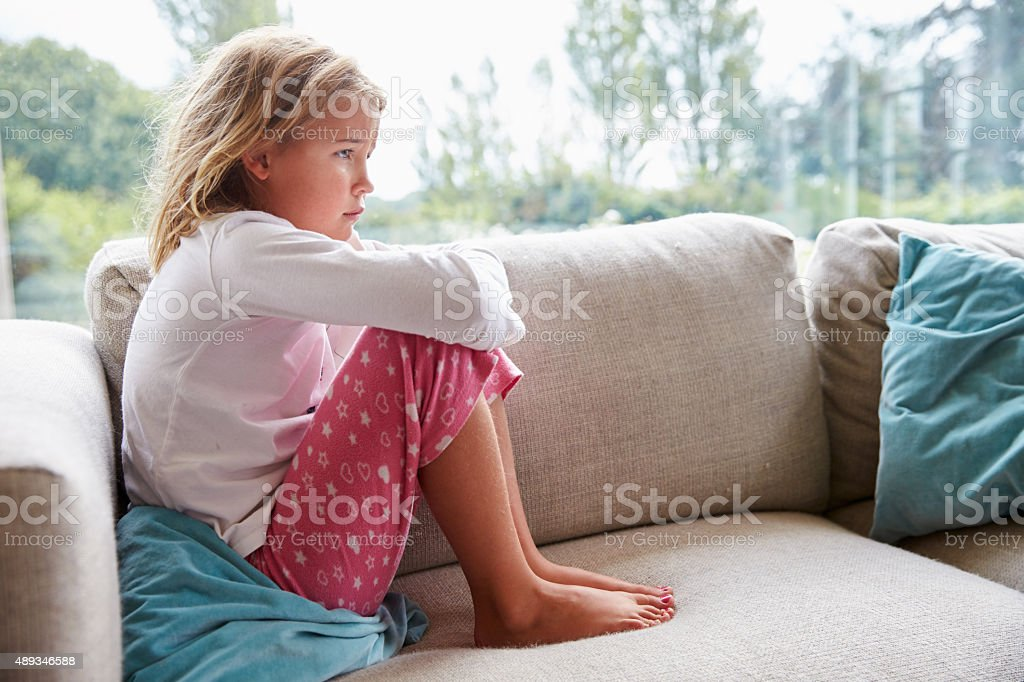 Unhappy Young Girl Sitting On Sofa At Home stock photo