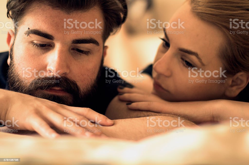 Unhappy young heterosexual couple in bedroom stock photo