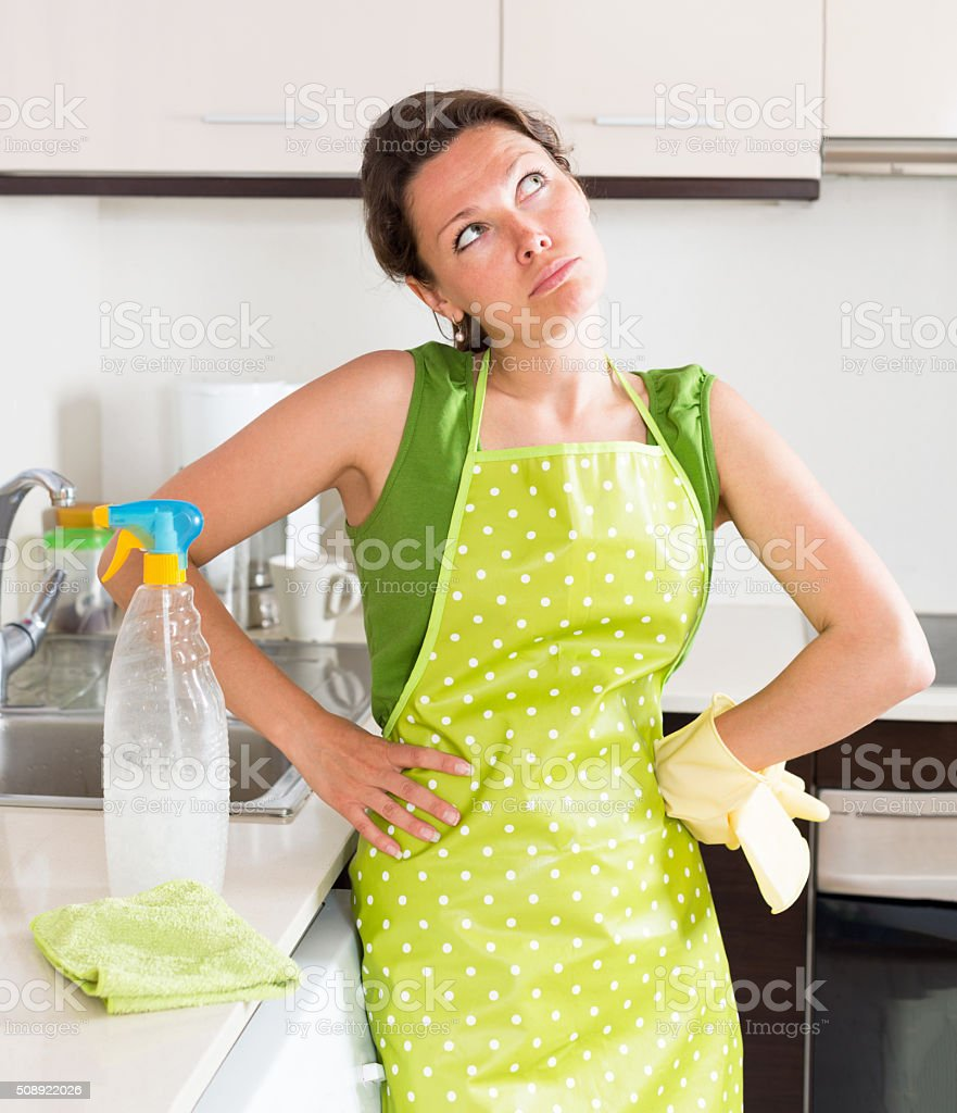 Unhappy young housewife cleaning furniture stock photo