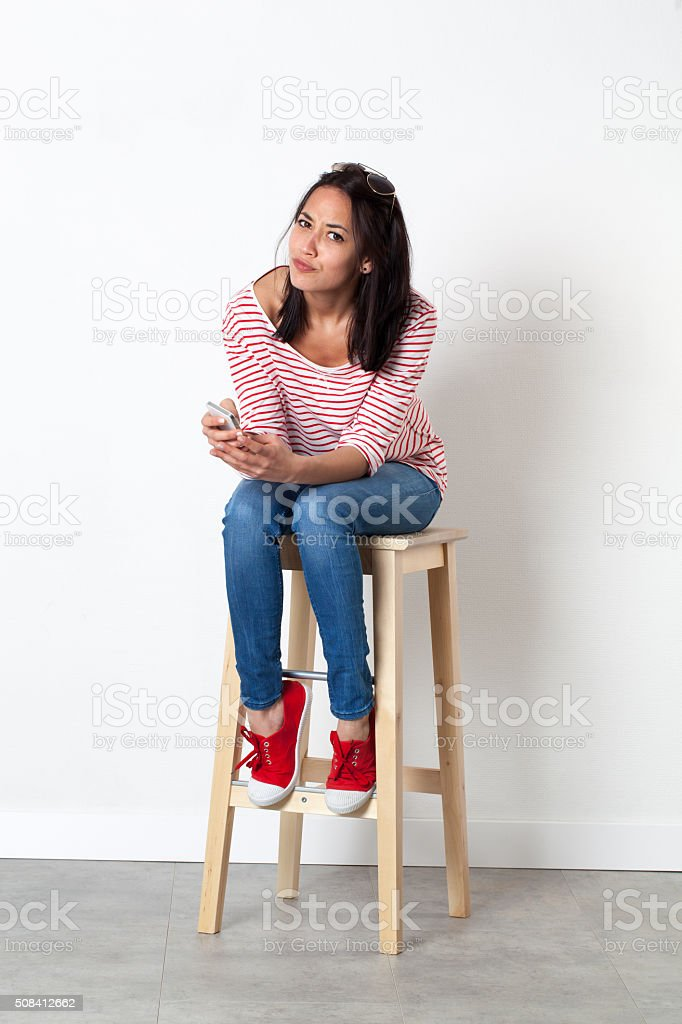 unhappy young multi-ethnic female student reading mobile messages stock photo
