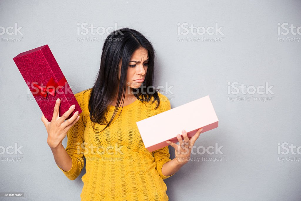 Unhappy young woman holding gift box stock photo
