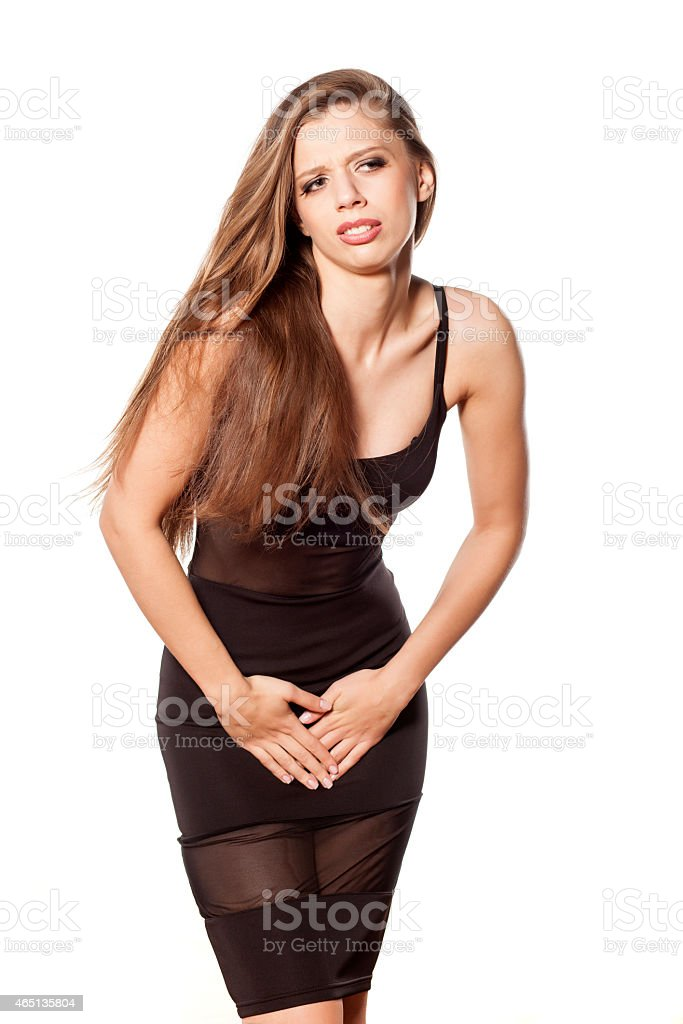 Unhappy young woman holding her hands in the groin stock photo