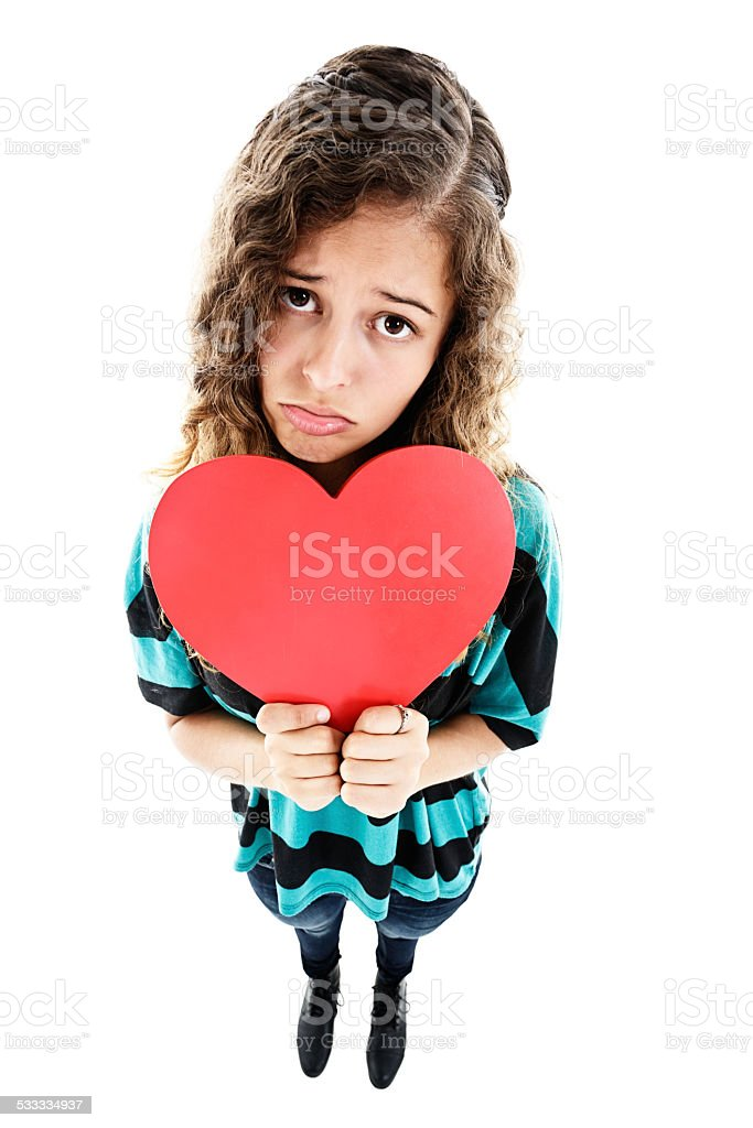 Unhappy young woman holds heart in exaggerated high-angle view stock photo