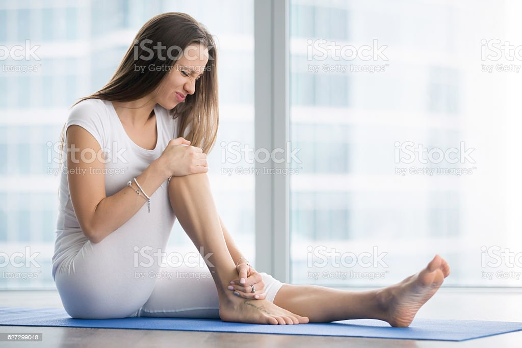 Unhappy young woman sitting on the mat stock photo