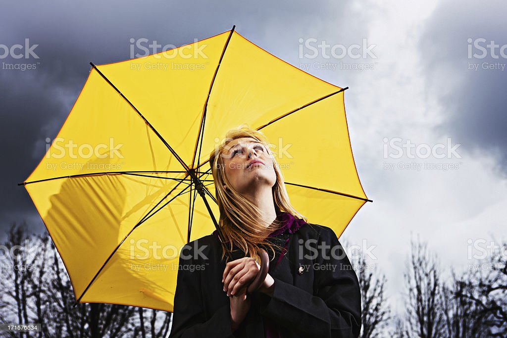 Unhappy young woman with umbrella waits for storm to pass royalty-free stock photo
