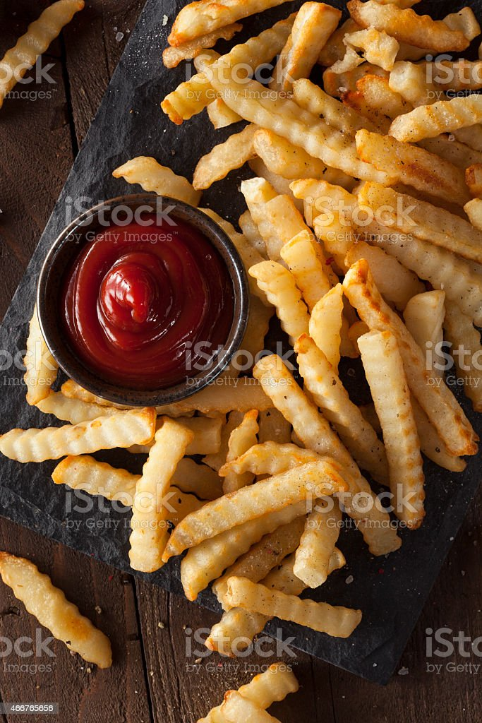 Unhealthy Baked Crinkle French Fries stock photo