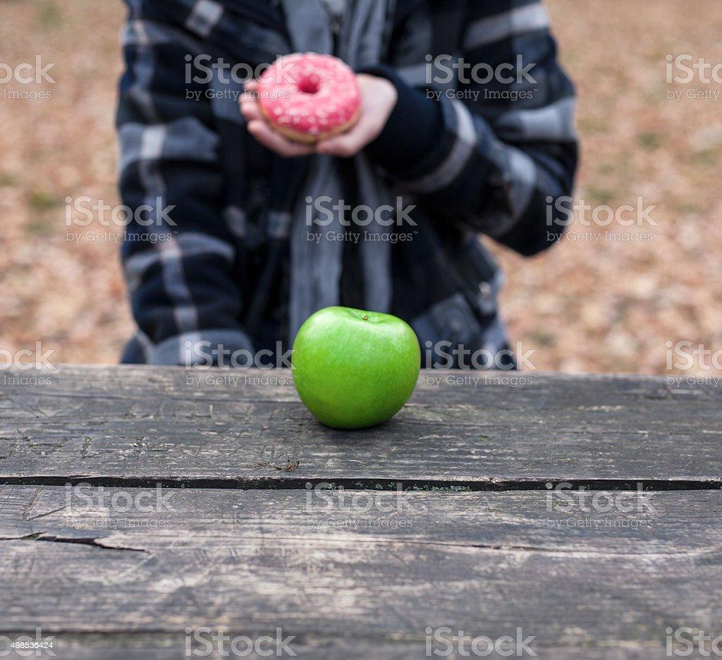 Unhealthy choice - doughnut over apple royalty-free stock photo