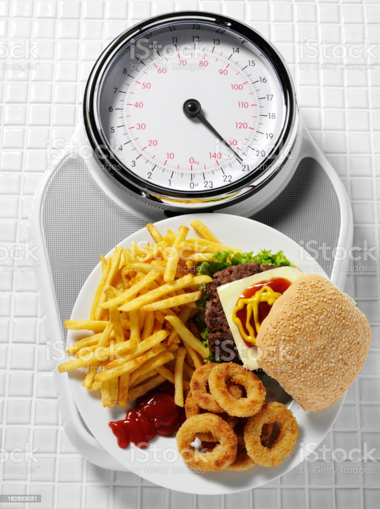 Unhealthy Eating on Bathroom Scales royalty-free stock photo
