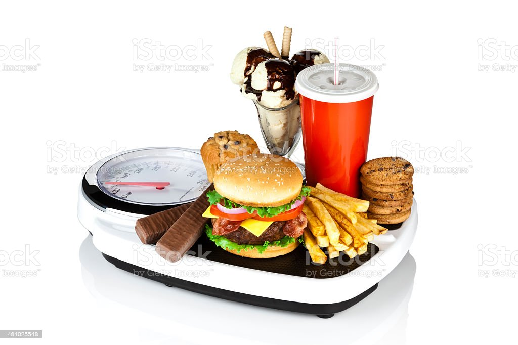Unhealthy food on weight scale isolated on white background stock photo