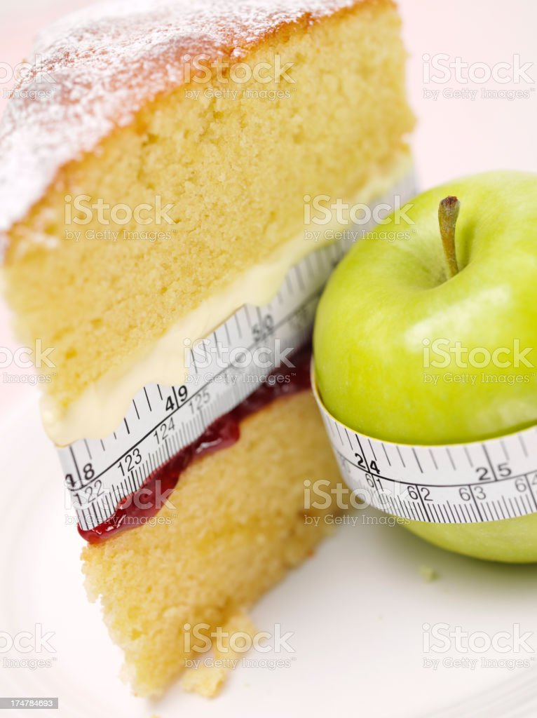 Unhealthy Sponge Cake and Healthy Apple royalty-free stock photo