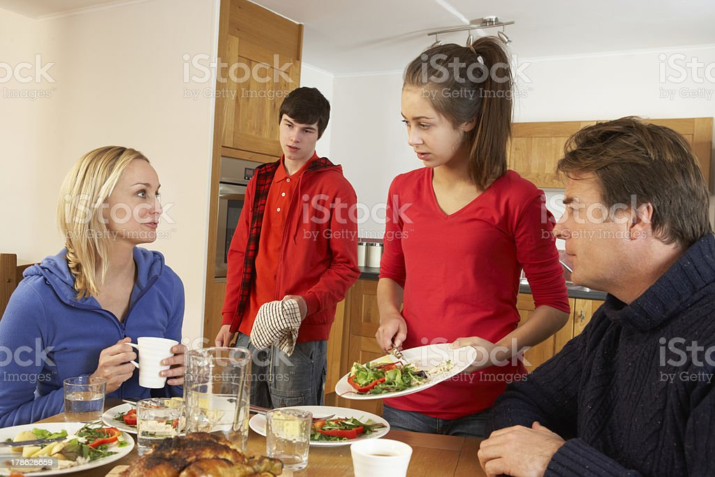 Unhelpful Teenagers Clearing Up After Family Meal In Kitchen royalty-free stock photo
