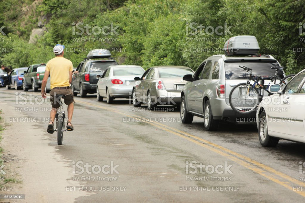 Unicycle Man Riding Road With Waiting Cars stock photo