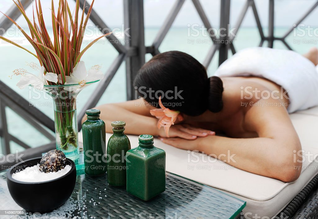 Unidentifiable woman lying face down on spa treatment bed stock photo
