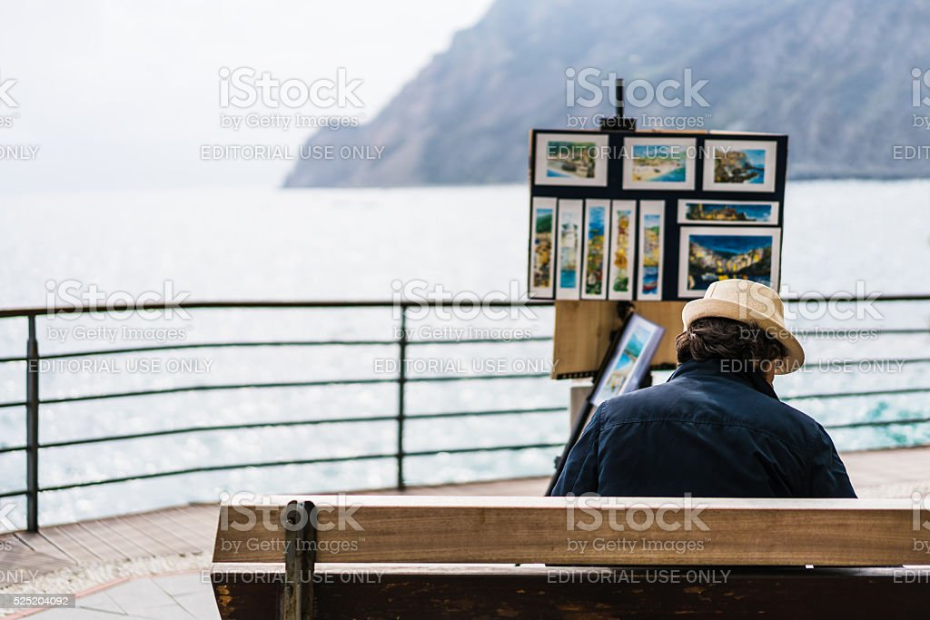 Unidentified artist selling landscape painting souvenirs at Monterosso, Italy stock photo