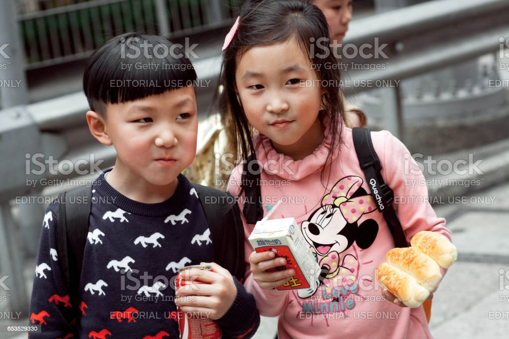 Unidentified boy and girl eating snacks outdoor on the way from school stock photo