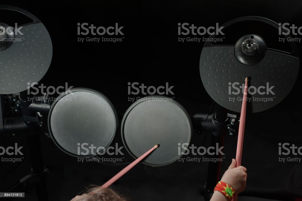 Unidentified Caucasian little girl play electronic drum stock photo