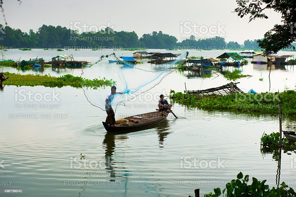 Unidentified fisher in a lake in An giang, Vietnam. stock photo