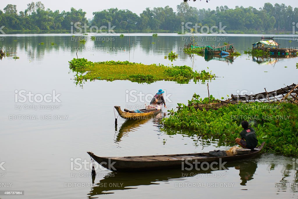 Unidentified fishers are in a lake in Angiang, Vietnam. stock photo