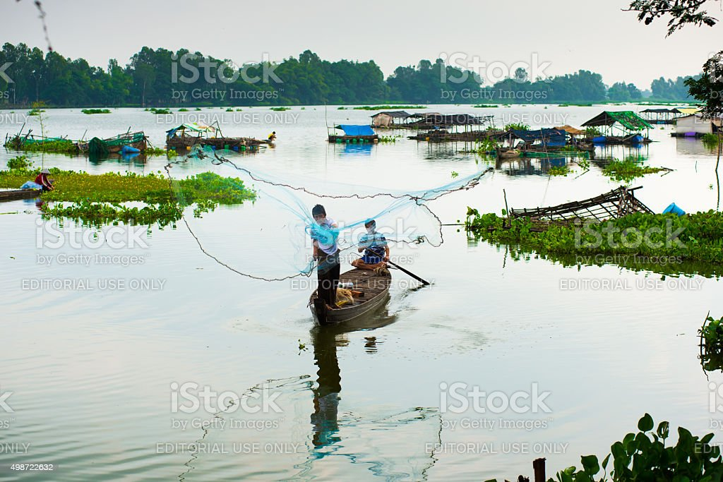 Unidentified fishers throw fish net to catch fish stock photo