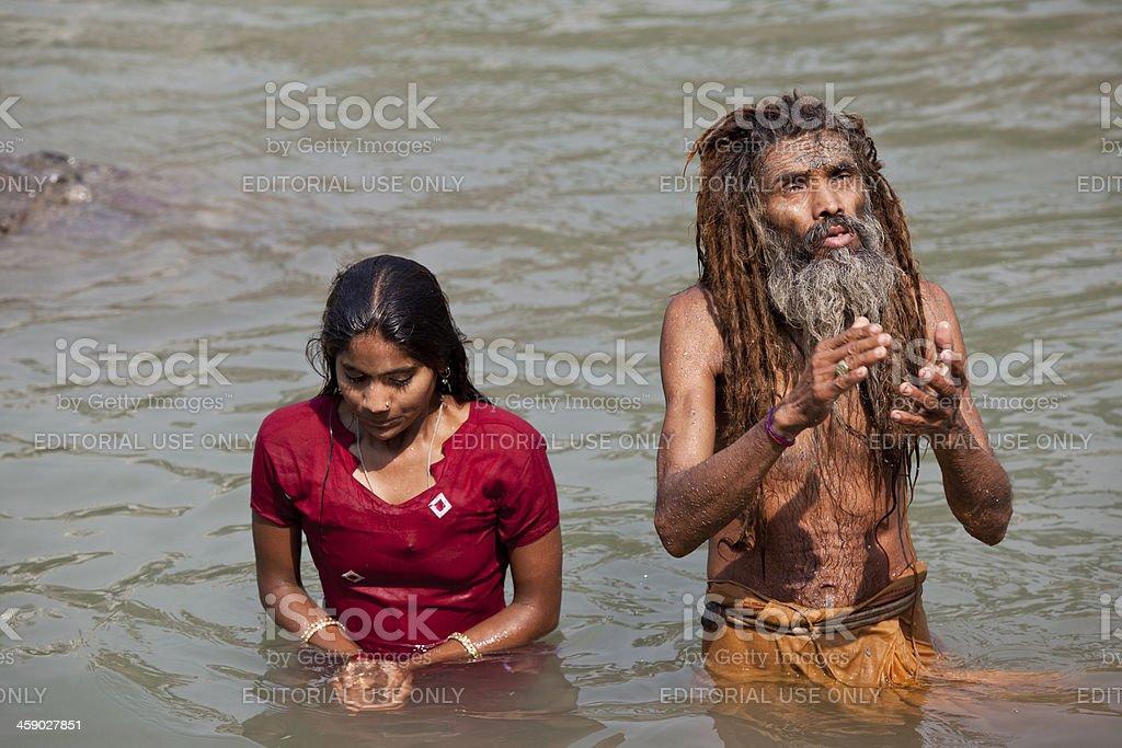 Unidentified hindu man and woman baths in holy Ganges River royalty-free stock photo