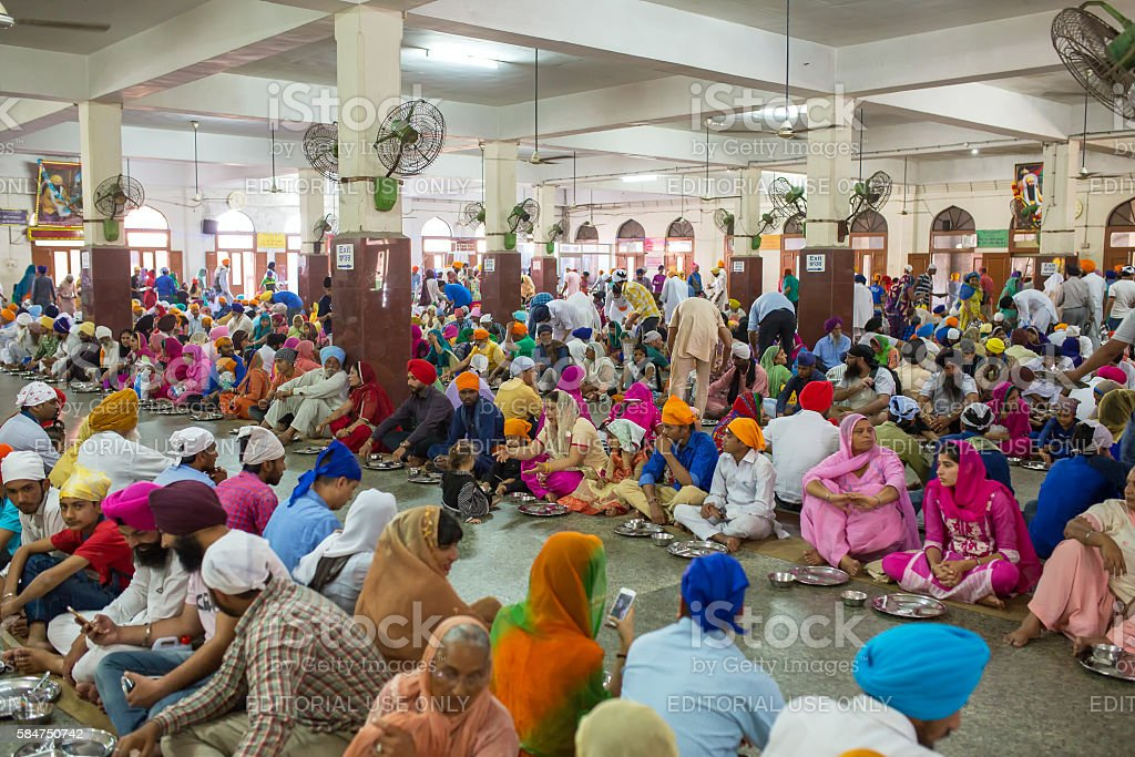 Unidentified indian people eating free food in the temple stock photo