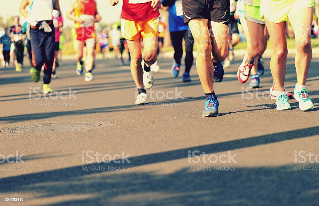 Unidentified marathon athletes legs running on city road stock photo