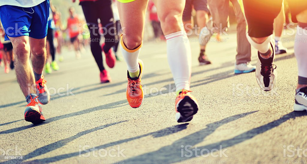 Unidentified marathon athletes legs running on city road stock photo