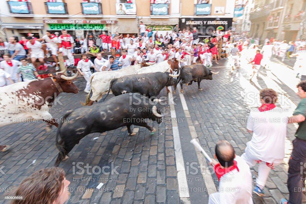 Unidentified men run from bulls in street in San Fermin stock photo