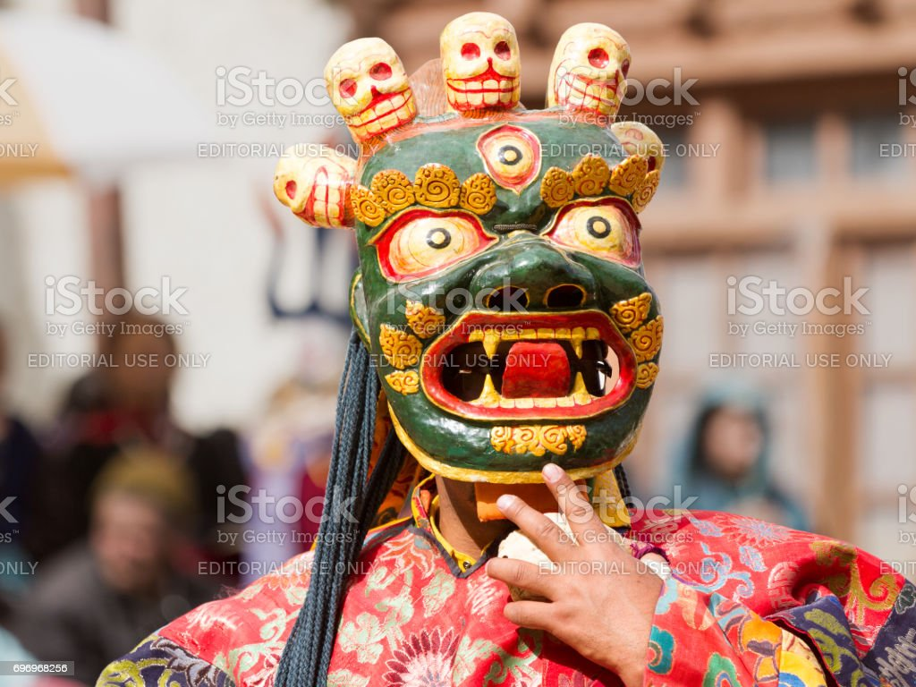 Unidentified monk in ritual mask performs a religious masked and costumed mystery dance of Tibetan Buddhism during the Cham Dance Festival stock photo