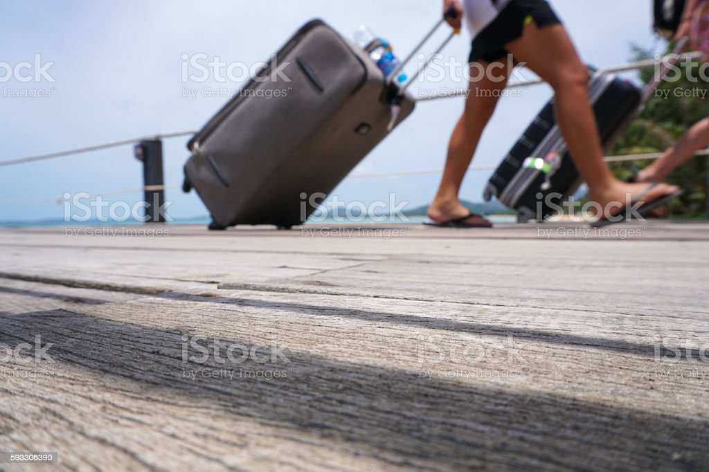 Unidentified passengers disembarking with luggage at pier, unfocused shot stock photo