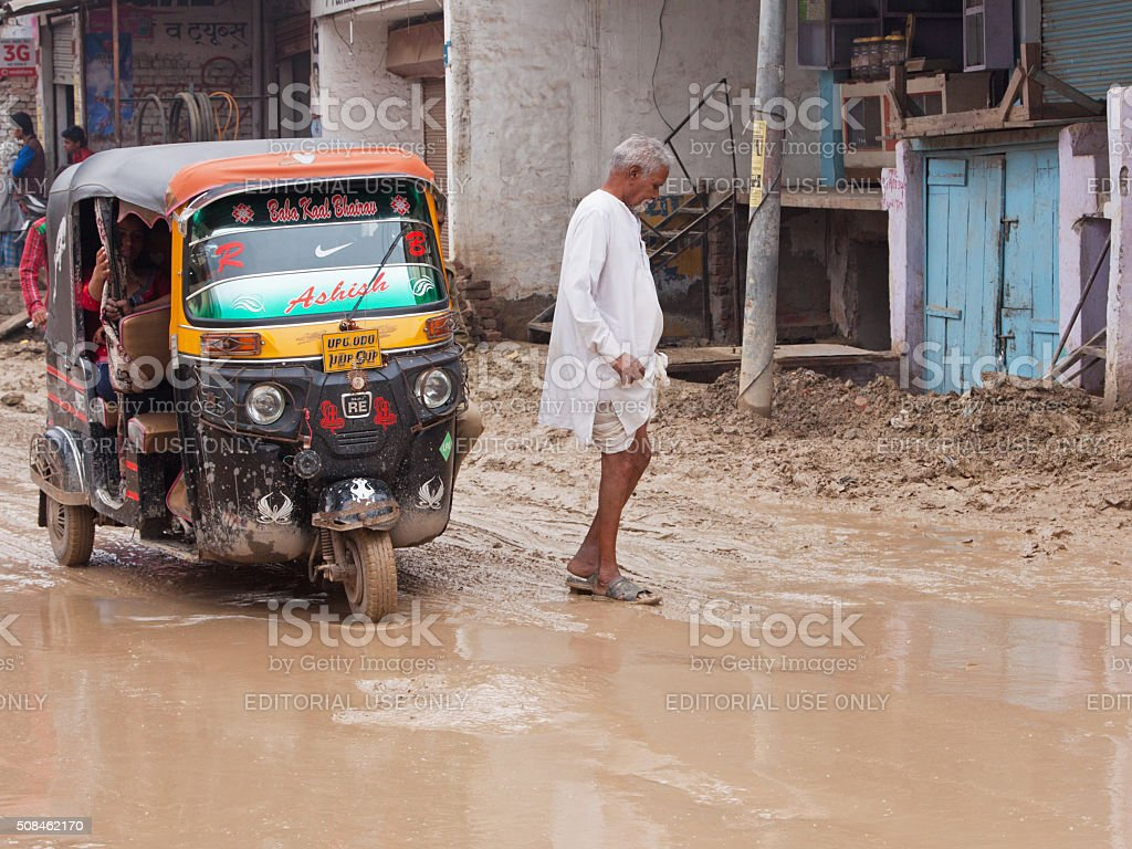 Unidentified pedestrian risking a soaking crossing an unsurfaced road, India stock photo