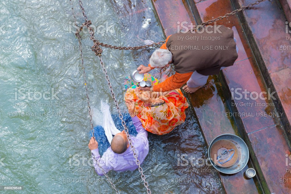 unidentified people bathing and taking ablutions in the Ganges River at the Holy ghats in Haridwar, India, sacred town for Hindu religion. stock photo