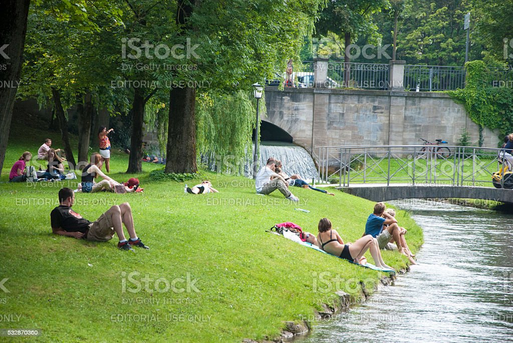 Unidentified people relaxing in the park in front of  river stock photo