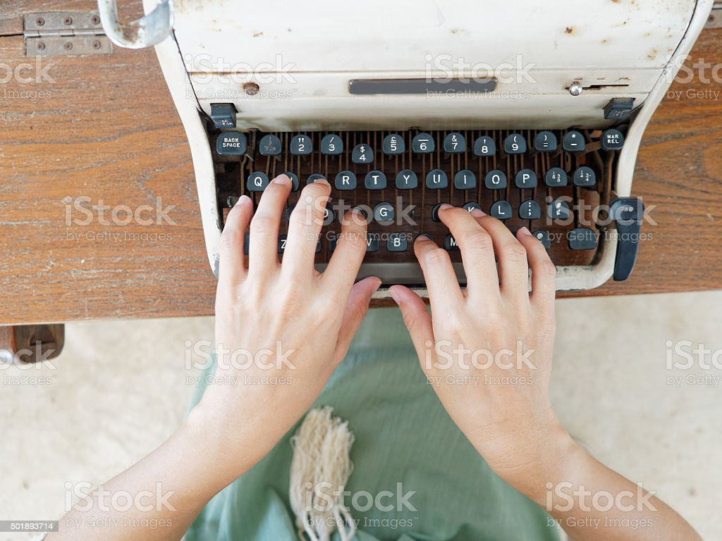 Unidentified person's hand typing on retro typing machine stock photo