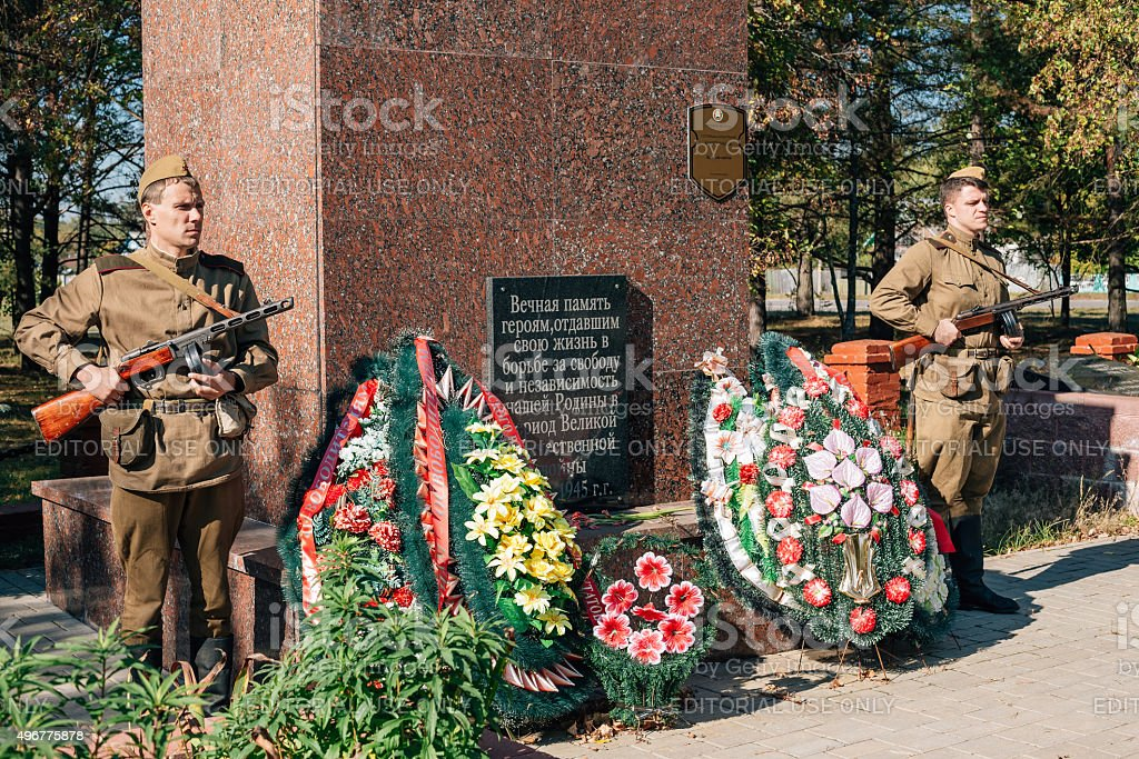 Unidentified re-enactors dressed as Soviet soldiers laying of wreath stock photo