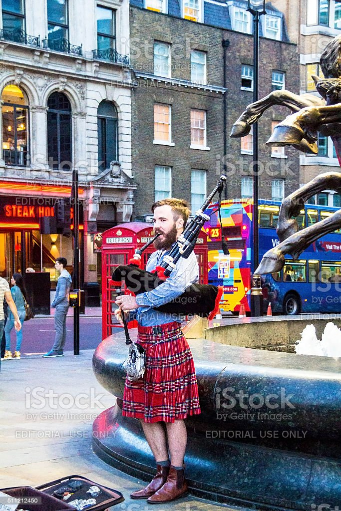 Unidentified Scottish young man with bagpipe at Piccadilly Circus. London stock photo