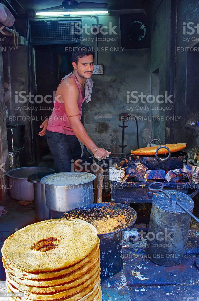 unidentified street vendor cooks at a  market stock photo
